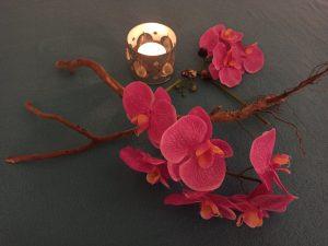 Schmuckbild mit Kerze und Blumen
